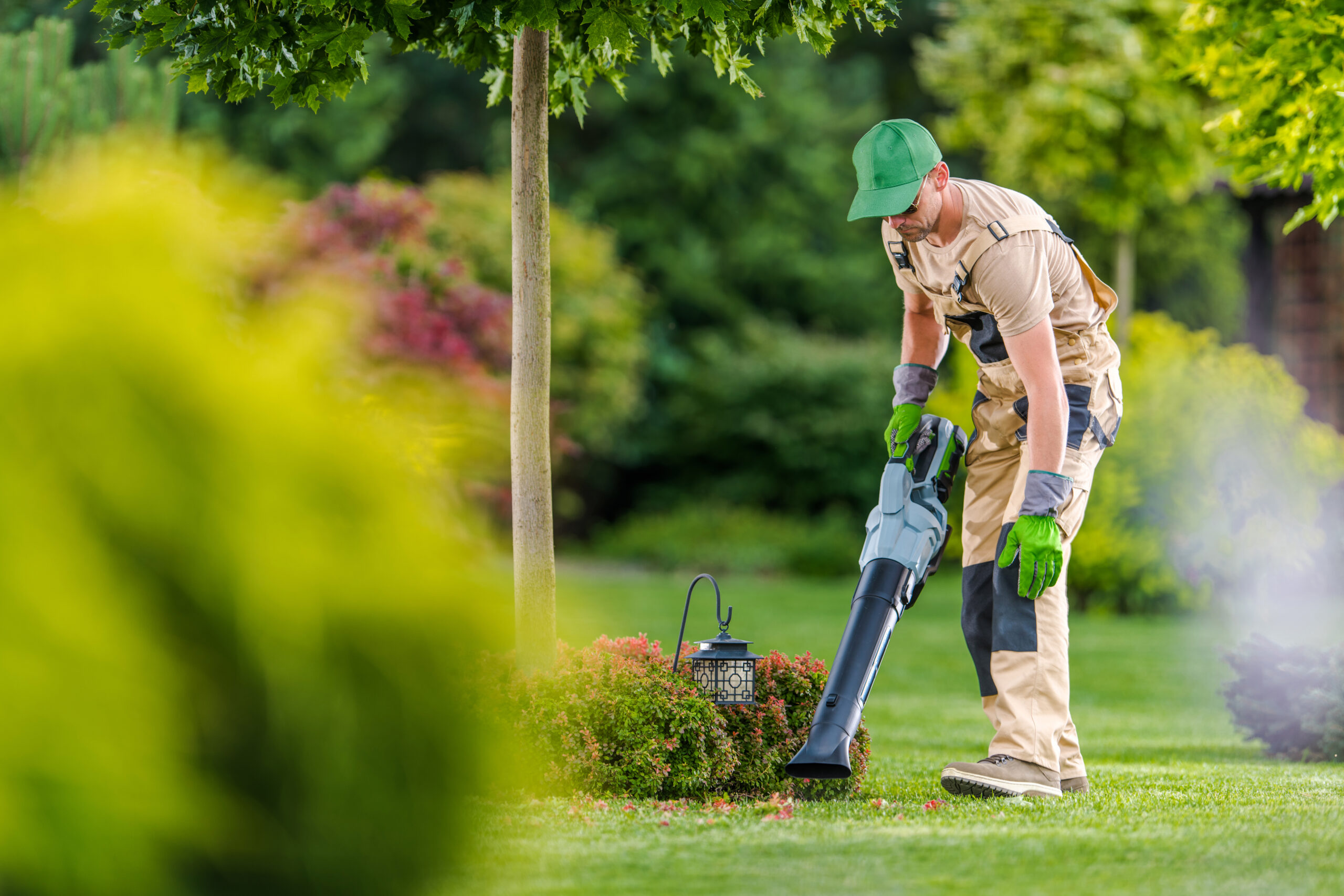Caucasian Gardener in His 40s Cleaning Backyard Garden Lawn Using Modern Electric Cordless Leaf Blower. Landscaping and Gardening Theme.