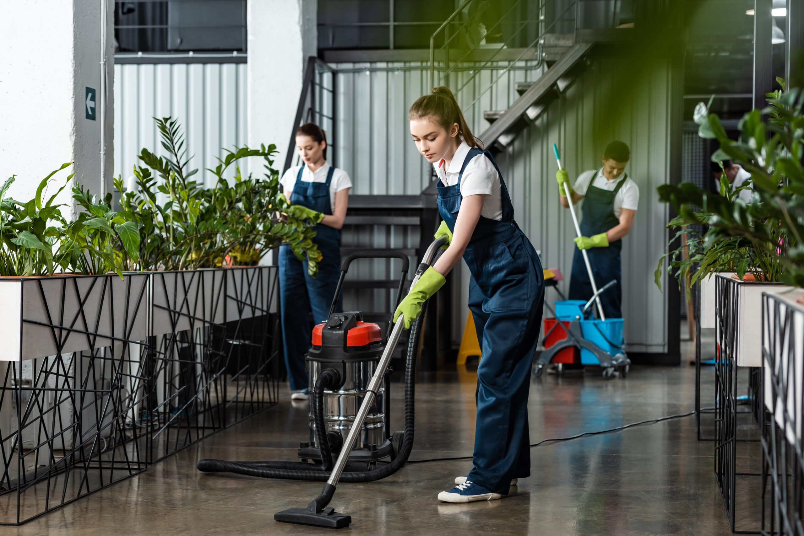 young cleaner vacuuming floor in office near colleagues